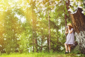 little girl takes pictures under a large blooming tree